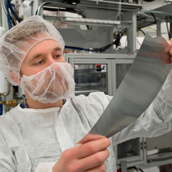 Worker inspecting material in cleanroom facility